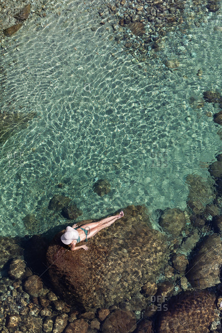 From above anonymous female in hat and swimwear lying on rock and resting in transparent water on summer day on resort