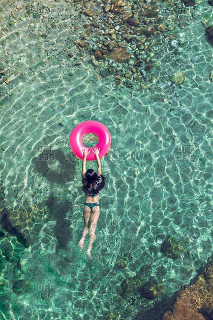 From above female in swimwear and sunglasses swimming in transparent water with inflatable tube on sunny day on resort