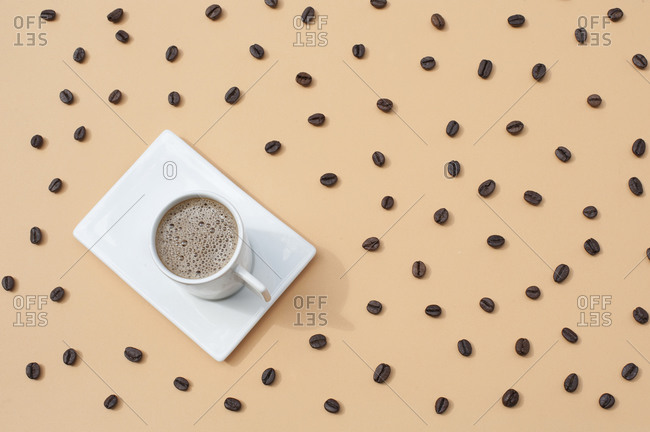 Top view composition of white ceramic mug with fresh hot coffee served on white tray on beige surface with scattered coffee beans