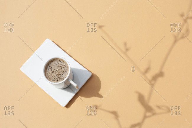 Top view of cup of hot black coffee placed on white plate on beige surface with shadow of plant branch