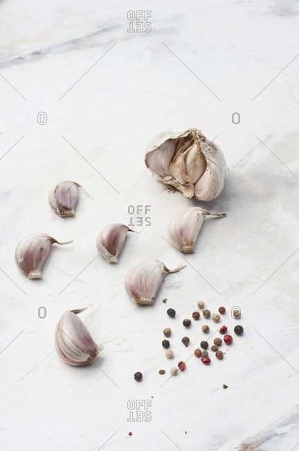 From above of unpeeled garlic cloves placed near assorted peppercorns on white marble surface