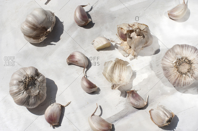 From above of unpeeled garlic cloves placed on white marble surface