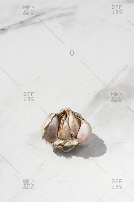 From above of unpeeled garlic clove placed on white marble surface