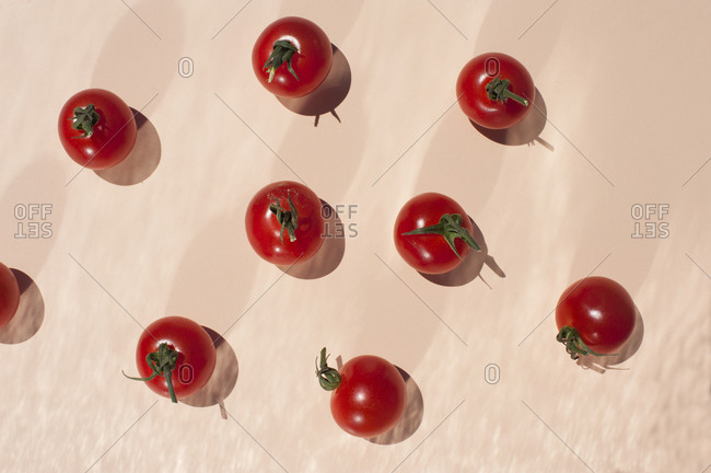 Top view of bunch of ripe red cherry tomatoes with green stems placed on beige background