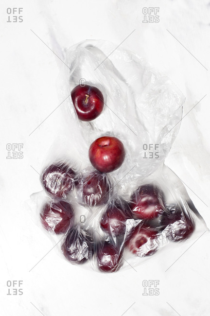 Top view of delicious ripe red cherry berries in transparent plastic sack placed on white table