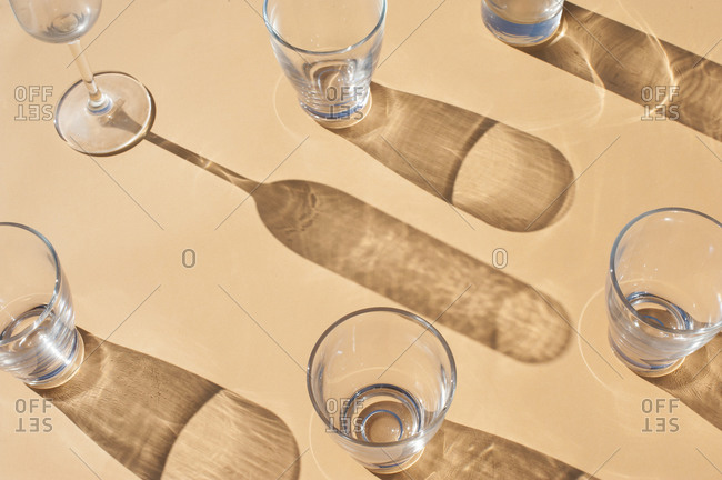 From above of transparent empty glass shots and goblet placed in sunlight on beige surface with shadows