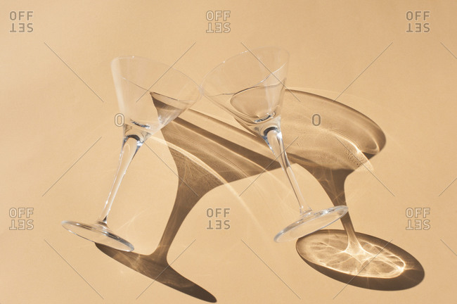 From above of transparent empty goblets placed in sunlight on beige surface with shadows