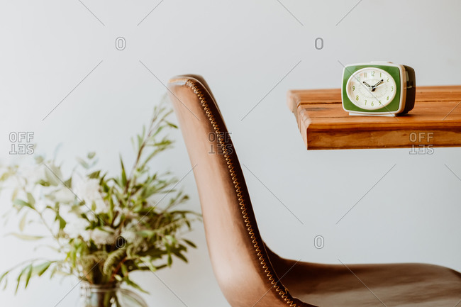 Vintage alarm clock placed on old lumber table in bright living room in apartment