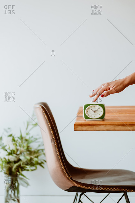 Unrecognizable female touching vintage alarm clock placed on wooden table in living room