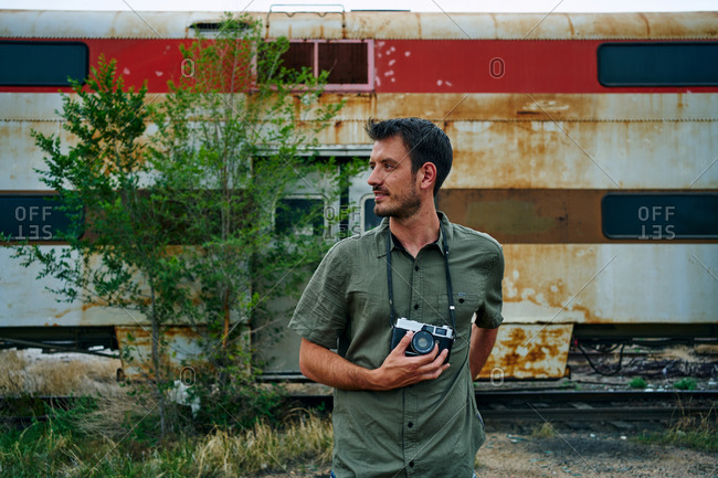 Traveling male photographer with vintage photo camera standing near abandoned rusty train in USA and looking away