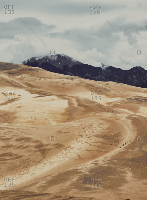 Majestic scenery of sand dunes and mountains under overcast sky in National Park in Colorado