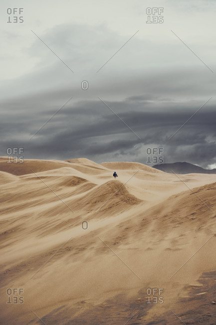 Unrecognizable tourist walking along dunes in Great Sand Dunes National Park during vacation in Colorado