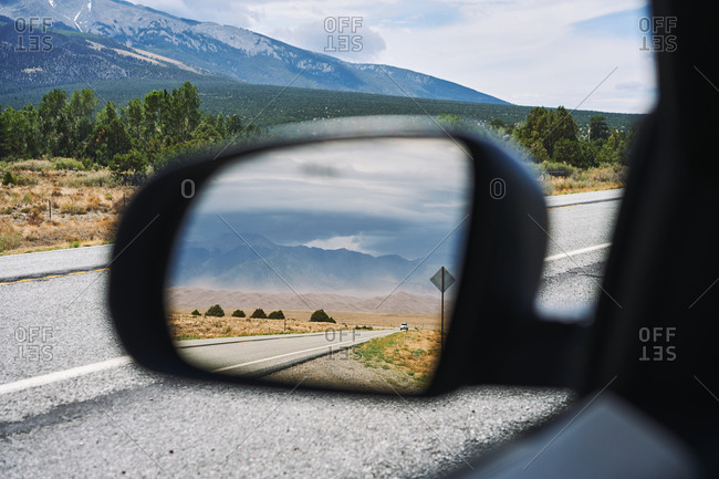Automobile driving along asphalt road on background of mountains and reflecting in side view mirror
