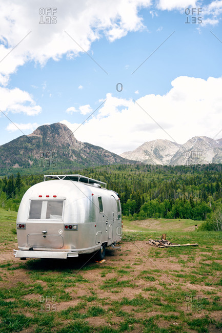 Travel trailer parked on green lawn on background of amazing landscape of mountain range and forest in USA