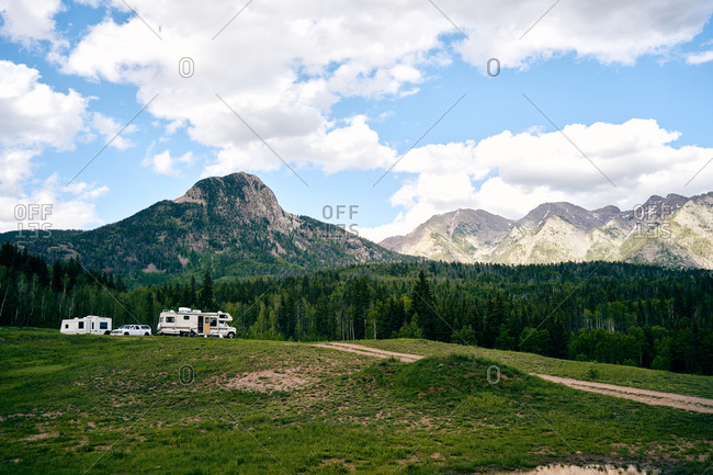 Majestic scenery of metal camper parked on lawn on background of magnificent forest and mountain ridge in USA