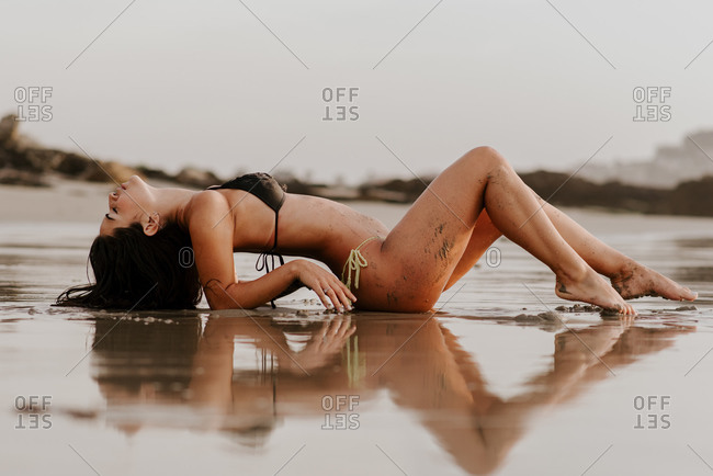 Sensual young female in bikini lying on mud while resting on wet beach
