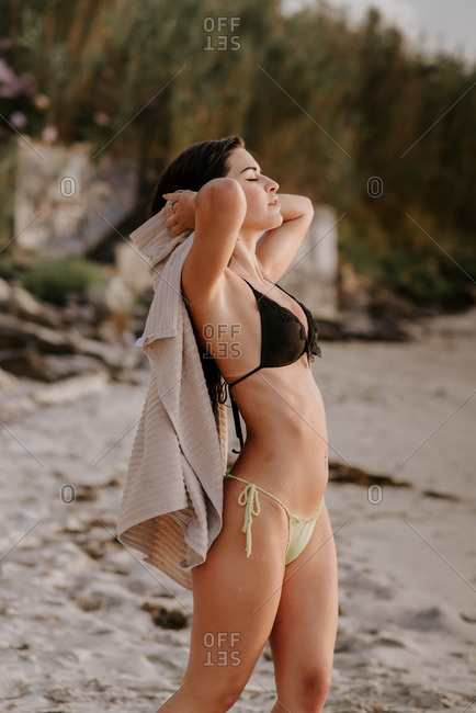 Fit brunette in swimwear looking at camera and wiping wet hair with towel while spending time on beach on summer day
