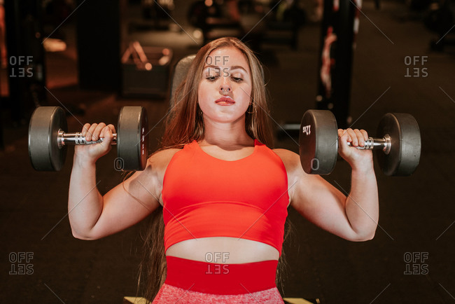 From above strong young sportswoman in bright red sportswear doing dumbbell chest press during functional training in modern gym