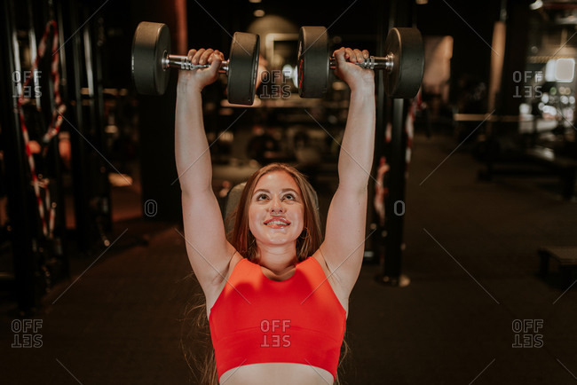 From above happy strong young sportswoman in bright red sportswear doing dumbbell chest press during functional training in modern gym