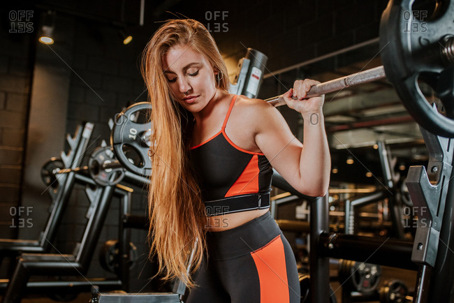Strong focused confident calm sportswoman athlete in sportswear working out with barbell in sport club