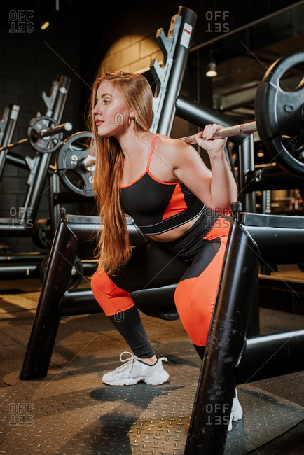 Crouched strong confident calm sportswoman athlete in sportswear working out with barbell in sport club