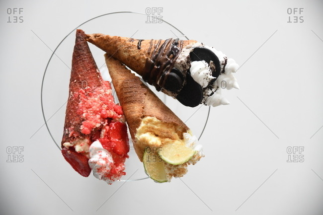 Three gourmet ice cream cones on light surface