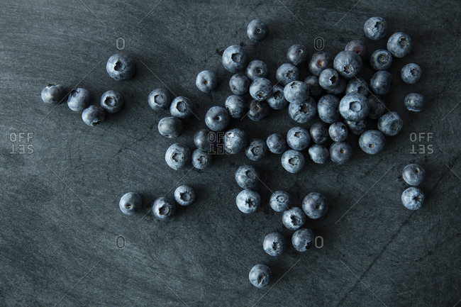Blueberries scattered on a dark background