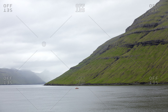 Boat in the distance off the coast of the Faroe Islands