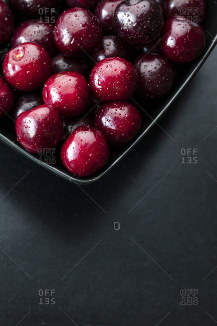 Wet cherries in a dish on a dark background