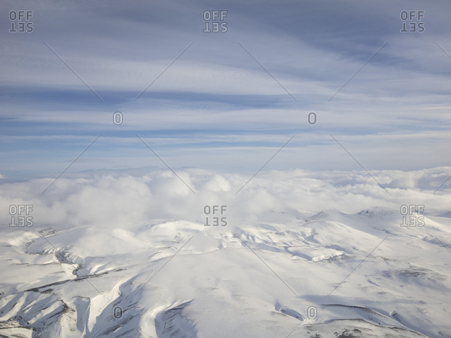 Cloudy sky over snow covered mountains in Iceland