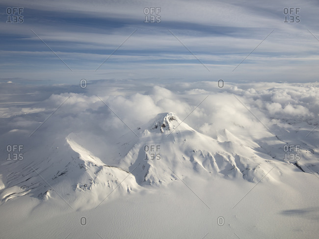 Snow covered mountain peak under cloudy skies in Iceland