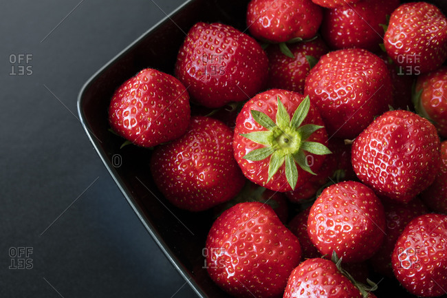 Strawberries in a dish on a dark background