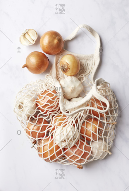 Onions and garlic in a mesh shopping bag