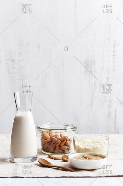 Almonds, almond milk, almond flour and almond butter in front of light background with copy space