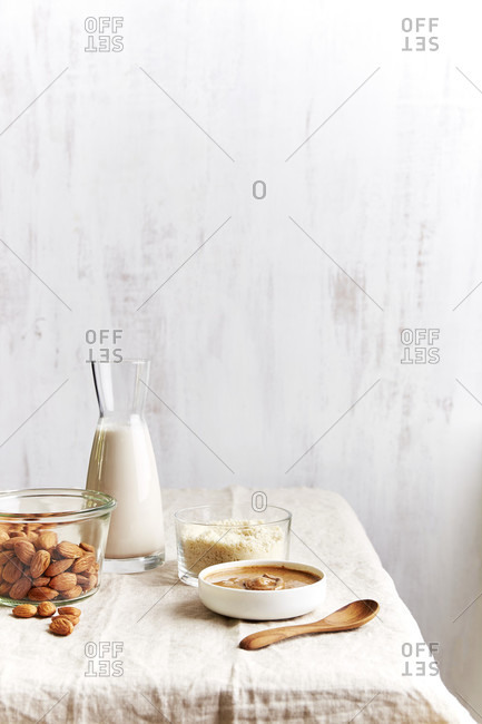 Almonds, almond milk, almond flour and almond butter on the edge of a table with copy space