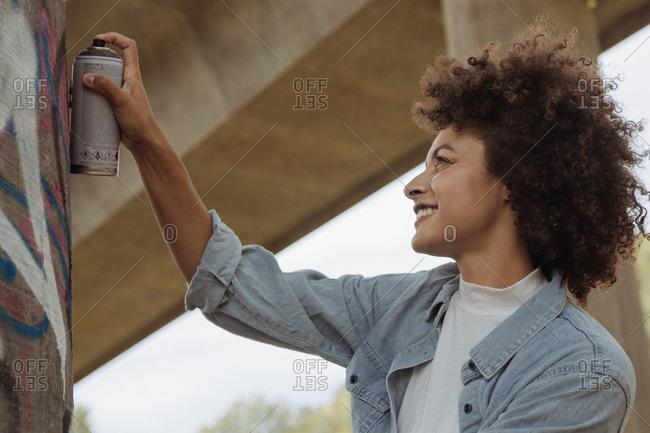 Female graffiti artist in urban city