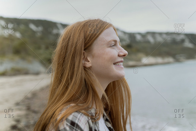 Woman with red hair looking out so sea on beach in winter