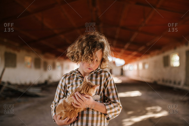 Curly blond haired boy with cat in his arms in an abandoned building