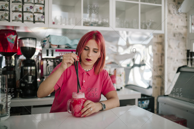 Young female waitress preparing a strawberry slush in an ice cream parlor