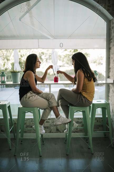 Two young women sharing a frozen shake in an ice cream parlor