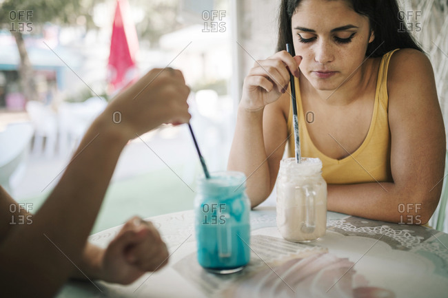 Young women having a frozen shake in an ice cream parlor