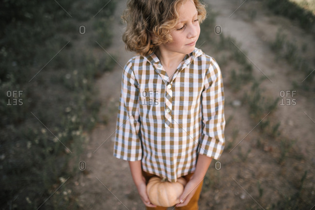 Curly-haired blond boy with pumpkin in hand