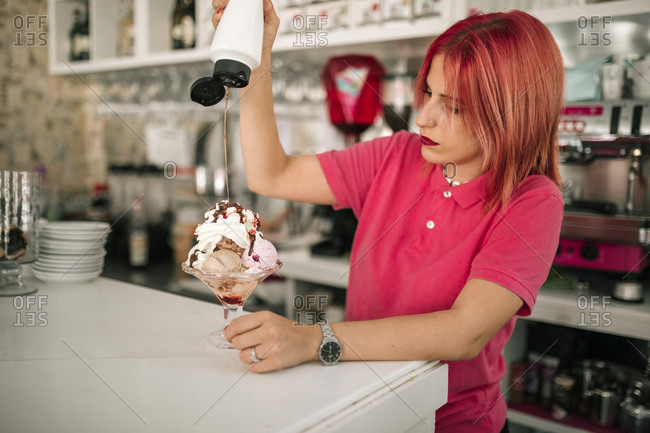 Young working woman pouring syrup to ice cream in a coffee shop