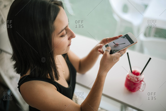 Young woman taking a photo with her mobile of a strawberry slush in an ice cream parlor