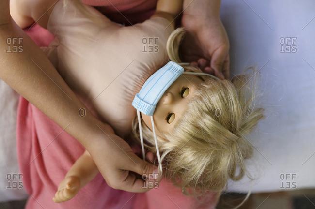 Girl (6-7) putting flu mask on doll
