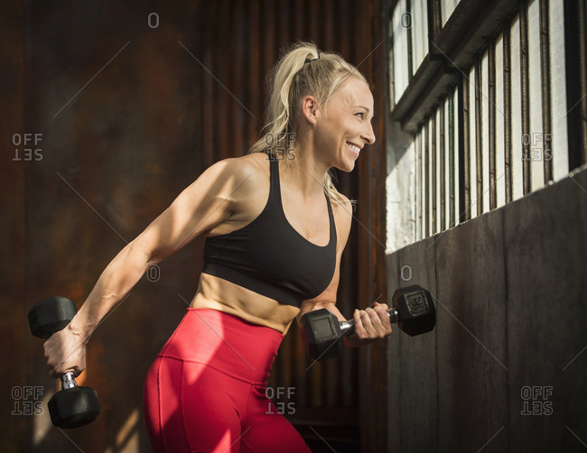 Sporty woman lifting dumbbells