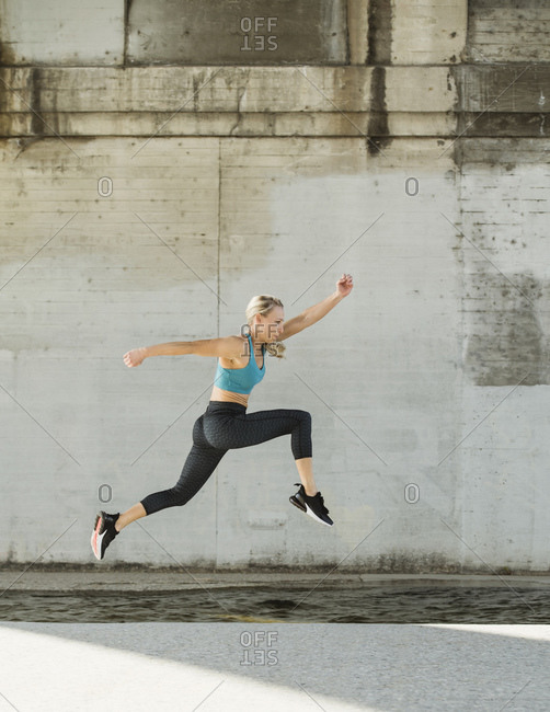 Sporty woman jumping outdoors