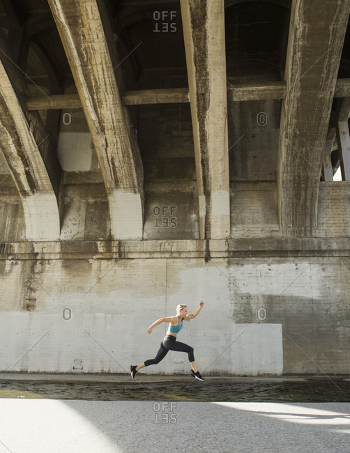 USA, California, Los Angeles, Sporty woman running underneath bridge