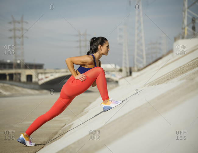 USA, California, Los Angeles, Sporty woman stretching in urban setting