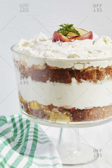 Trifle dessert with whipped cream and peaches